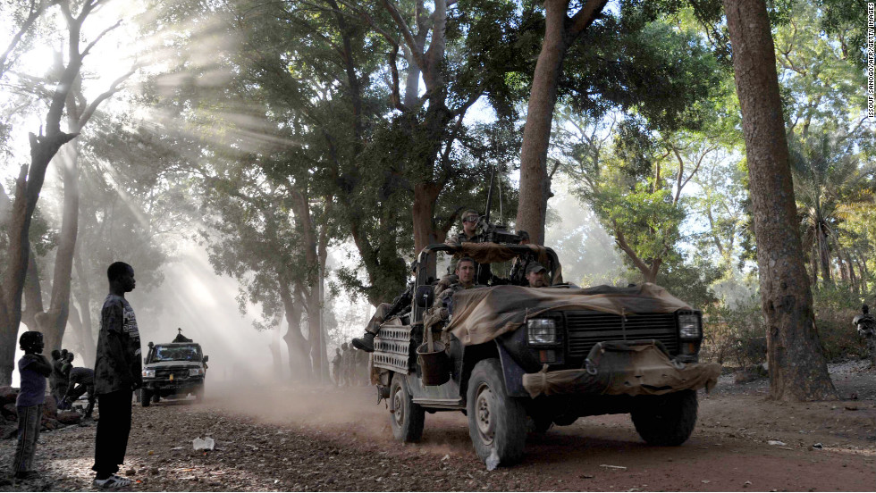 Malian youths look on as French soldiers drive through Niono on Sunday, January 20.