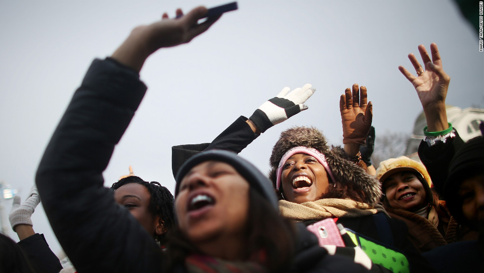 People cheer at a television camera on the National Mall before the inauguration ceremony Monday in Washington.