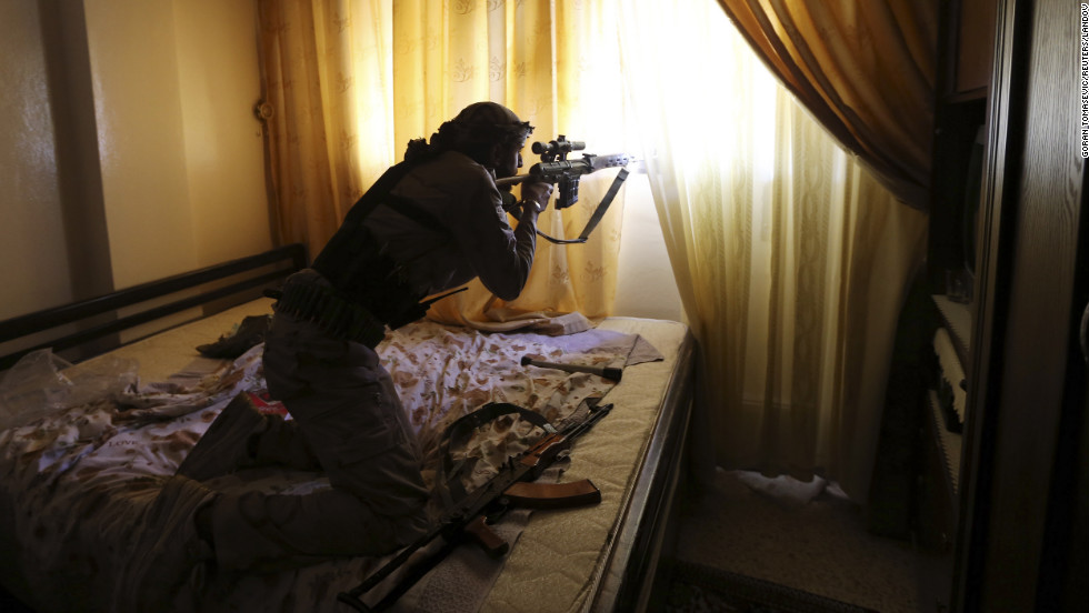 A Free Syrian Army fighter fires from inside a house during heavy fighting in Damascus on January 22.