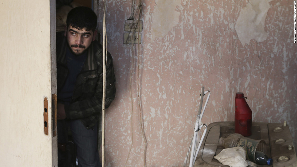 A Free Syrian Army fighter moves inside a house in Haresta neighborhood of Damascus on Sunday, January 20.