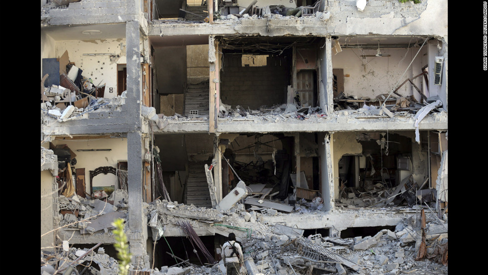 Missing exterior walls of a building reveal homes in the Mieha suburb of Damascus on Monday, January 21.