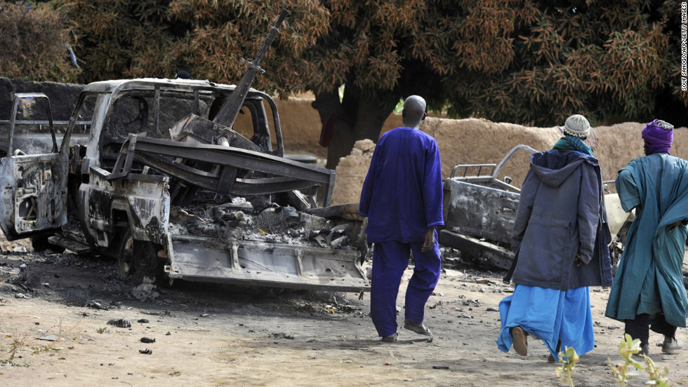 Malians walk past a destroyed truck mounted with a machine gun on Tuesday, January 22. The truck was used by militants and destroyed during airstrikes by the French air force.