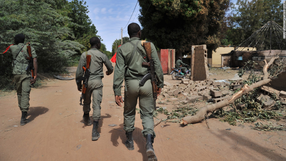 Malian soldiers walk past destroyed army barracks as they patrol in Diabaly on January 22, 2013.