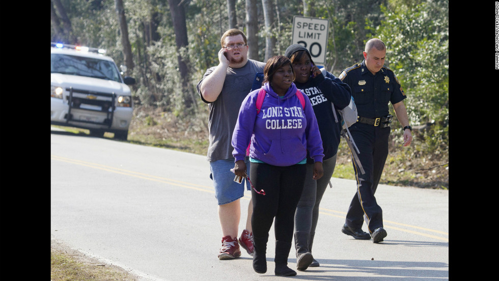 Students evacuate the area with a sheriff's deputy near the college's North Harris campus. There were more than 10,000 students on the campus at the time of the shooting, spokesman Jed Young said.