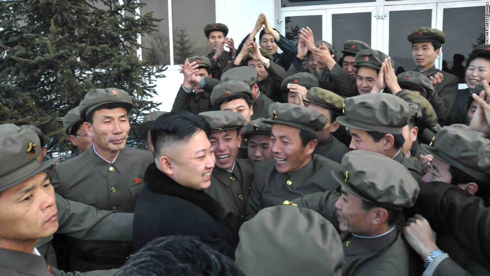 In a photo released by the official North Korean news agency in December 2012, Kim celebrates a rocket's launch with staff from the satellite control center in Pyongyang.