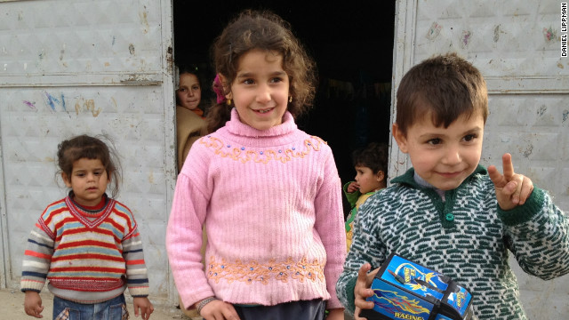 Children stand outside a building housing Syrian refugees in Hacipasa, Turkey.