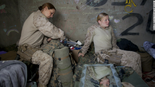 Hospital Corpsman Shannon Crowley packs for a mission as Lance Cpl.. Kristi Baker sits on her bed in 2010 in Afghanistan.