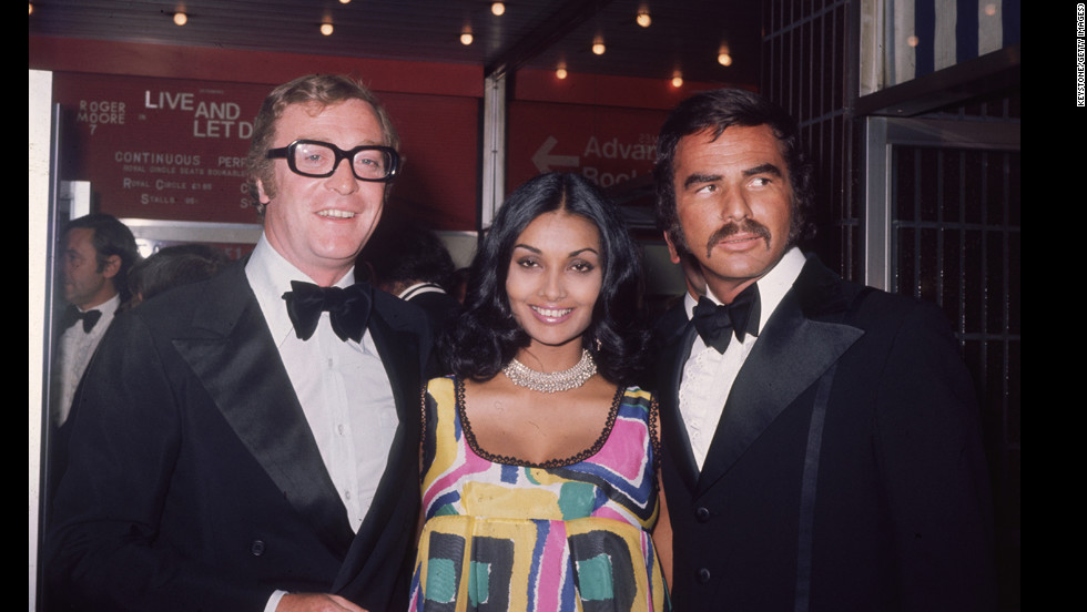 "Reynolds attends the premiere of ""Live and Let Die"" in 1973 with Michael Caine and his wife Shakira Caine."