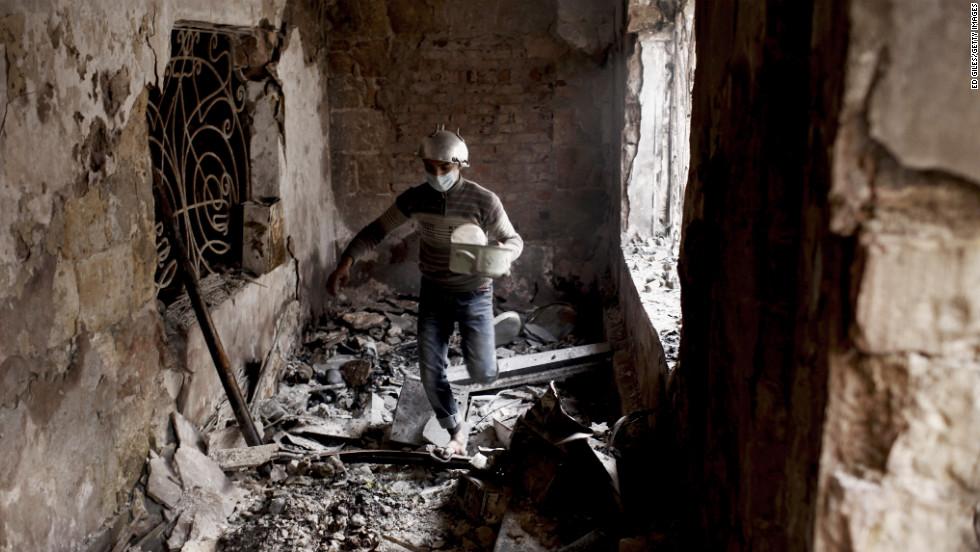 A protester walks through a damaged school building.