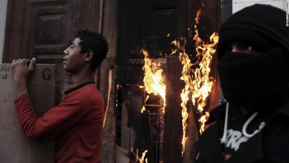 Egyptian protesters stand by the burning door of a school building on January 26, in Cairo.