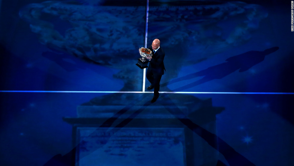 Four-time Australian Open men's singles champion Andre Agassi carries the Norman Brookes Challenge Cup before the men's final match on January 27.