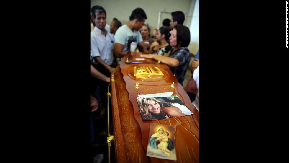 A coffin decorated with a photograph and image of the Virgin Mary is surrounded by mourners.