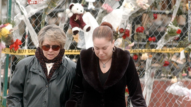 A woman grimaces as she is led away from a makeshift memorial in West Warwick, Rhode Island.