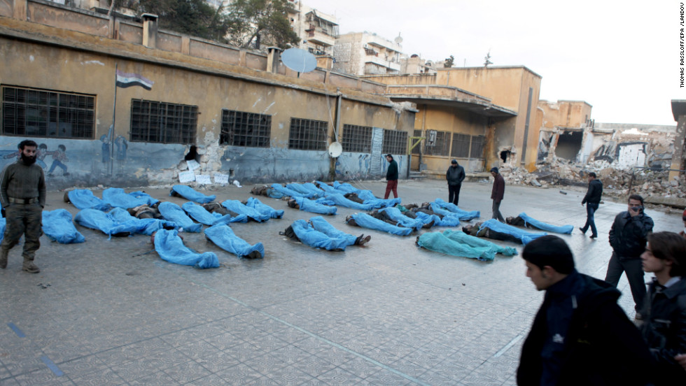 Bodies in blue plastic bags lie in a school courtyard while residents try to identify missing relatives.
