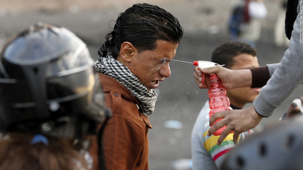 A protester sprays water into the eyes of a man after his exposure to tear gas during clashes with police near Cairo's Tahrir Square on Tuesday, January 29.