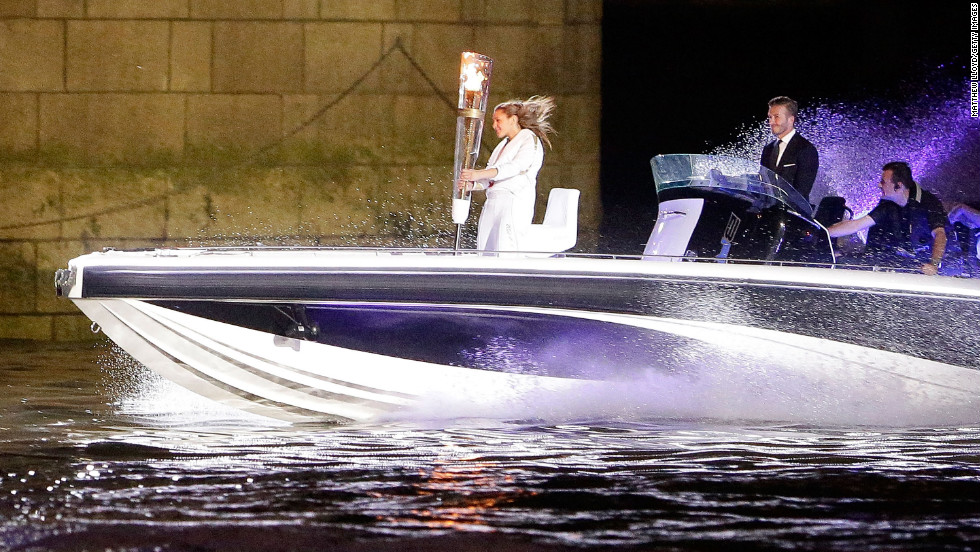 Beckham passes under London's Tower Bridge in a speedboat carrying the Olympic Torch in 2012.