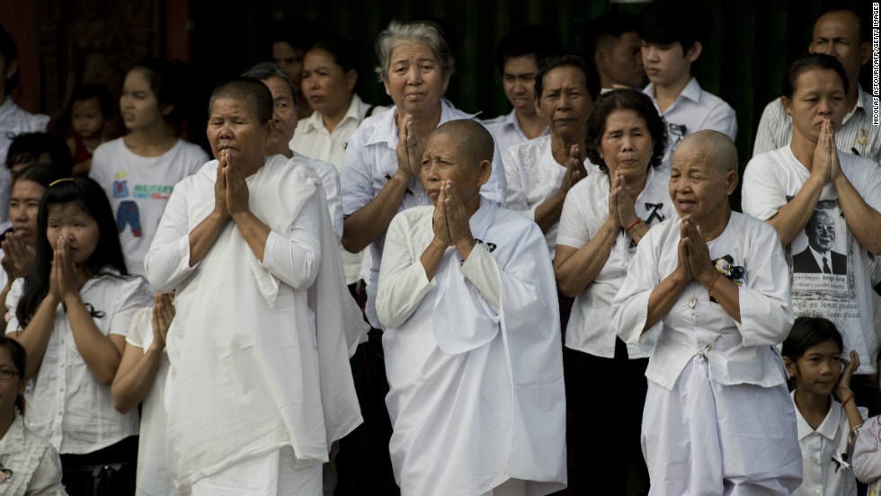 Cambodians pray as they look on at the funeral procession of the late former King Norodom Sihanouk on Friday.