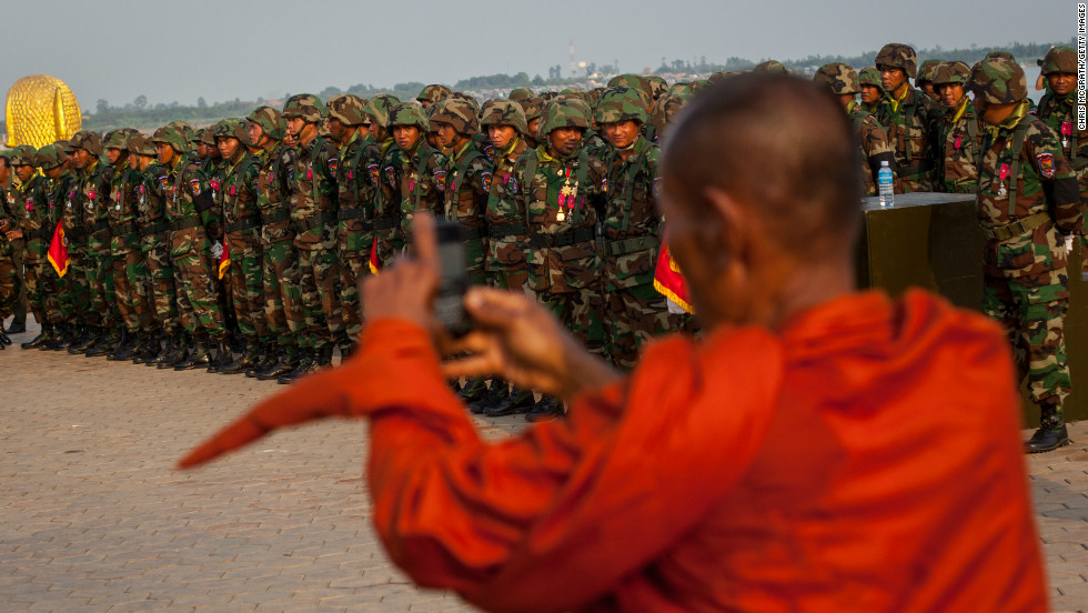 A monk takes photographs of the military as they rehearse for the funeral of former King Norodom Sihanouk outside the Royal Palace on Thursday.