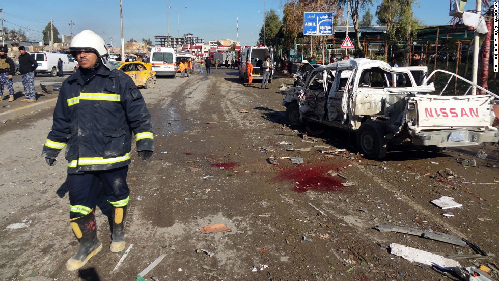 An Iraqi firefighter walks past the scene of a car bombing followed by an assault on a police headquarters, which killed at least 20 people in the disputed northern city of Kirkuk, Iraq, on Sunday, February 3.