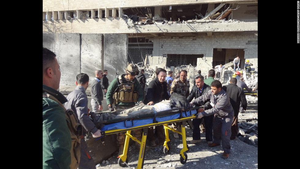 Iraqi rescuers wheel a stretcher from the scene.