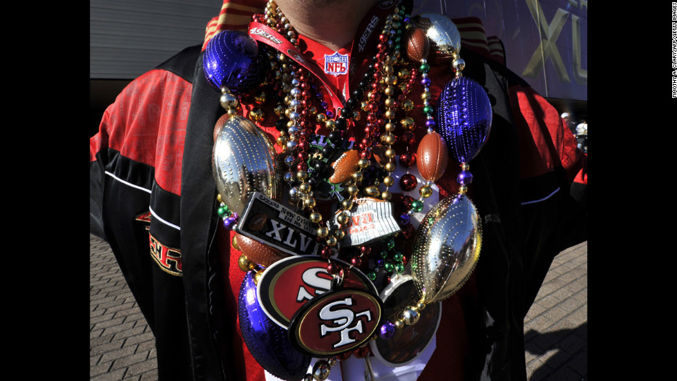 A 49ers fan is weighed down with team paraphernalia poses outside the Superdome before the start of the game.