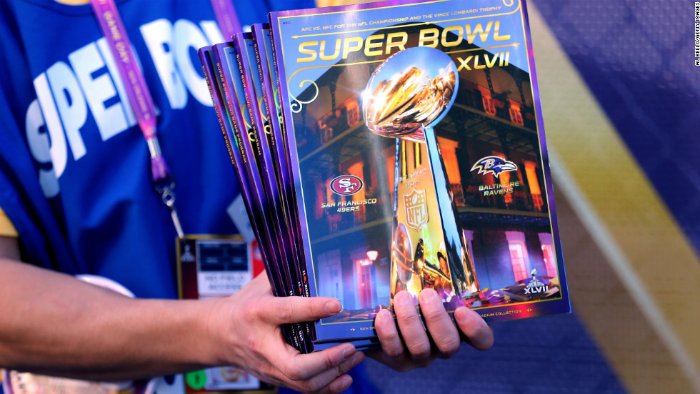 Super Bowl programs are sold outside the stadium as fans stream into the Superdome.
