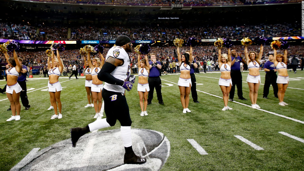 Veteran Baltimore Ravens linebacker Ray Lewis runs onto the field as cheerleaders and fans cheer.