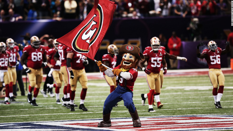 49ers mascot Sourdough Sam waves a flag on the field as players take the field shortly before kickoff.