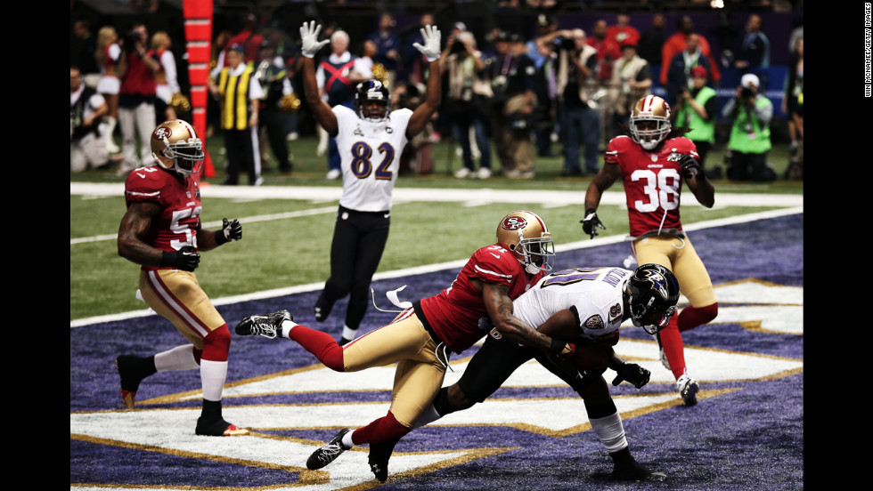 Donte Whitner of the 49ers tries to defend Anquan Boldin of the Ravens.