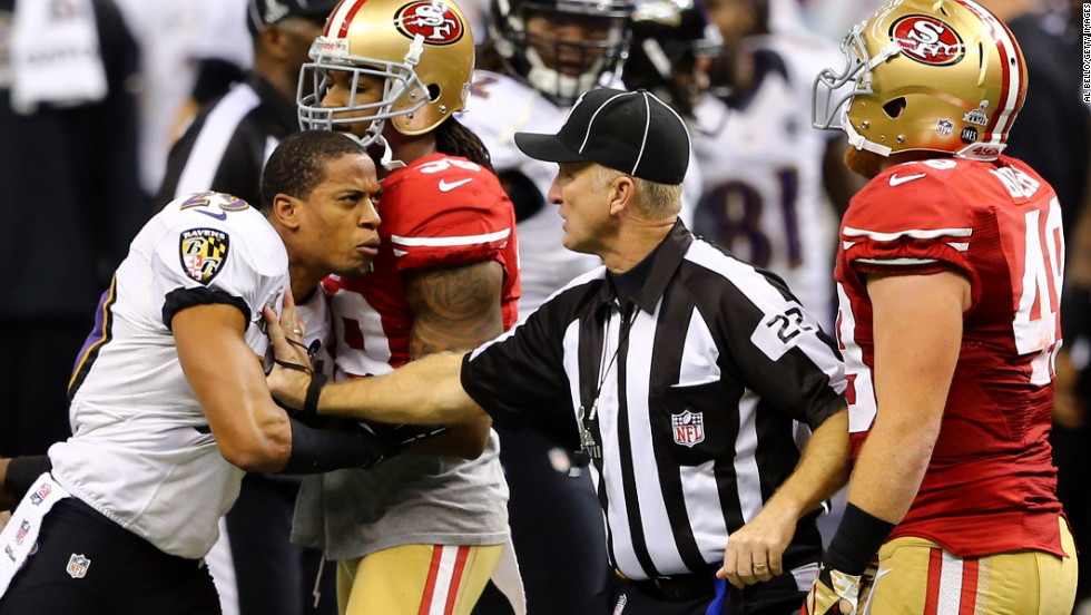 Baltimore Ravens cornerback Cary Williams reacts angrily after a play as head linesman Steve Stelljes and 49ers fullback Bruce Miller attempt to hold him back.