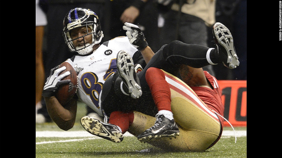 Ed Dickson of the Baltimore Ravens is brought down by Donte Whitner of the San Francisco 49ers.