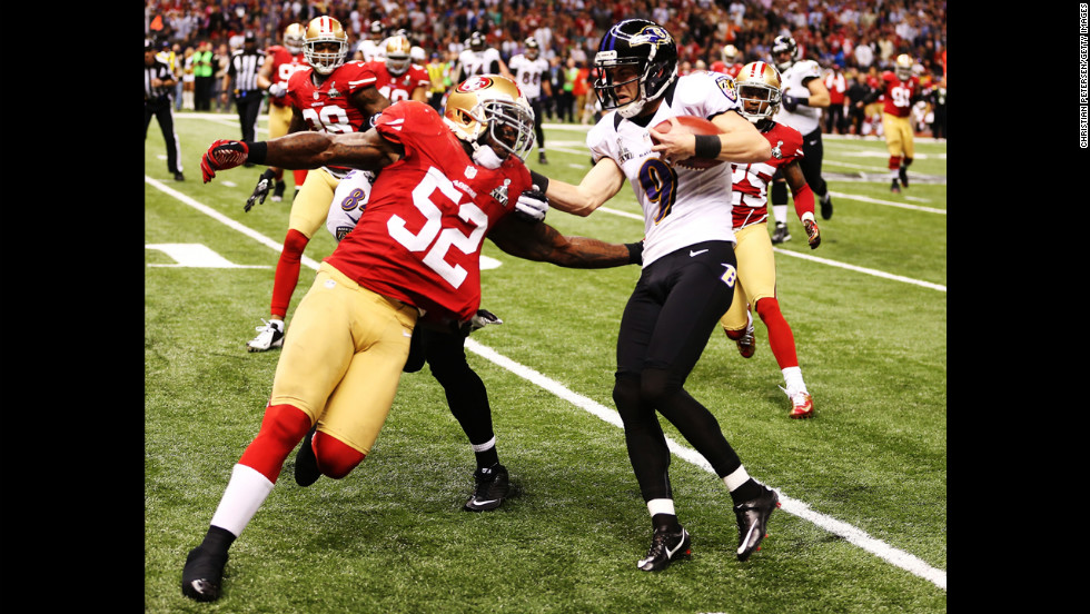 Kicker Justin Tucker of the Baltimore Ravens is stopped short of a first down on a fake field goal attempt in the second quarter. Patrick Willis is the tackler.