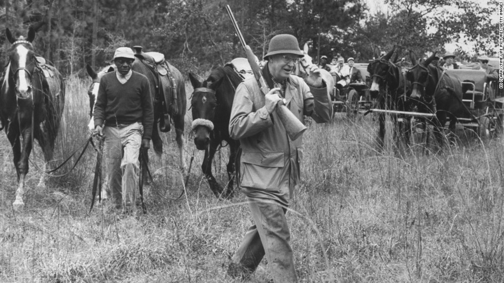 Dwight D. Eisenhower totes a gun on a quail hunting trip at the plantation of his first secretary of the Treasury, George Humphrey, in Georgia in January 1961.