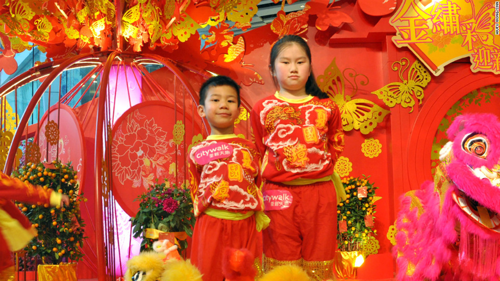 "A standard lion head weighs about five pounds, or 2.2 kilograms. A more traditional head is about twice that weight.<br /><br />These young and proud performers, Keong Ka Ching (left) and Chiu Po Ying, ages five and nine respectively, are only old enough to play the ""baby lion."""