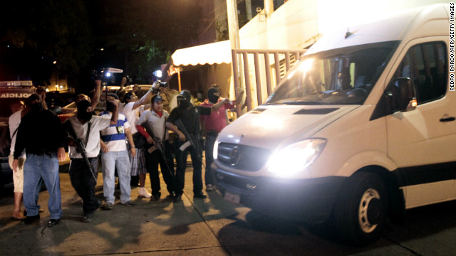 Police escort a van with twelve Spanish citizens and a Mexican woman in Acapulco on February 4, 2013.