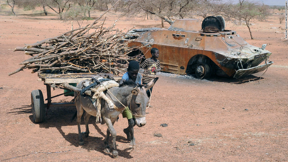 A child leads a donkey cart past a destroyed Malian army armored vehicle near Douentza, Mali, on February 5.