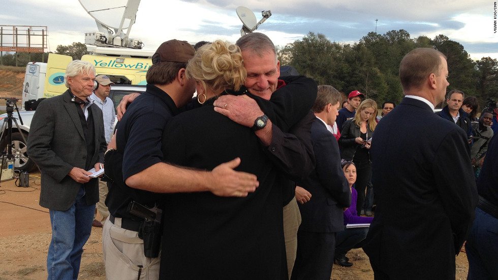 Dale County Schools Superintendent Donny Bynum hugs Dale County Sheriff Wally Olson and an unidentified woman after the standoff.