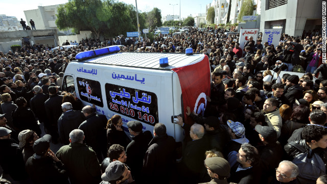 People surround an ambulance transporting the body of Tunisian opposition leader and outspoken government critic Chokri Belaid, from from a clinic in Tunis to the public hospital for an autopsy, after he was shot dead with three bullets fired from close range, on February 6, 2013. Tunisian Premier Hamadi Jebali called the assassination 'an act of terrorism', as the country grapples with growing political instability. AFP PHOTO / FETHI BELAID (Photo credit should read FETHI BELAID/AFP/Getty Images)