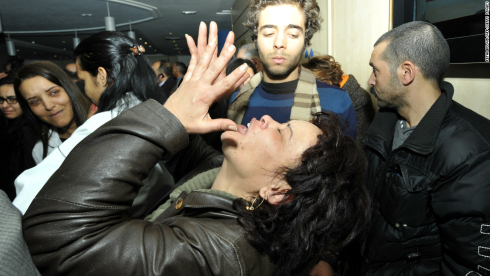 A woman mourns after the death of Tunisian opposition leader in Tunis.
