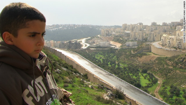 Emad's son Gibreel looks over at the Israeli settlements