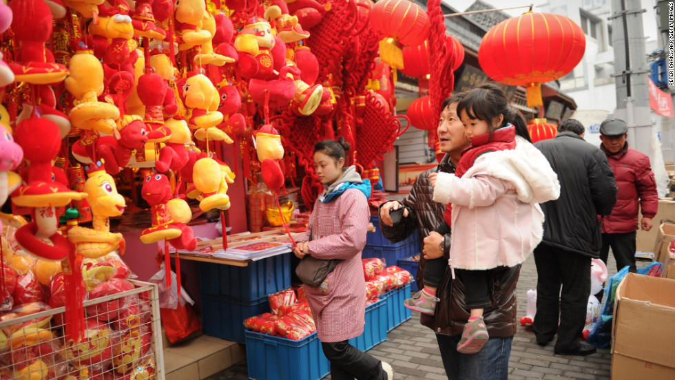 A father and daughter look at toy snakes at a market in Shanghai on February 6.