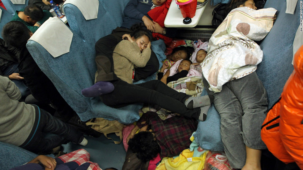 People sleep in their seats on a packed train from Guangzhou to Changchun as they make their way back home for the Chinese New Year on Monday, January 28.