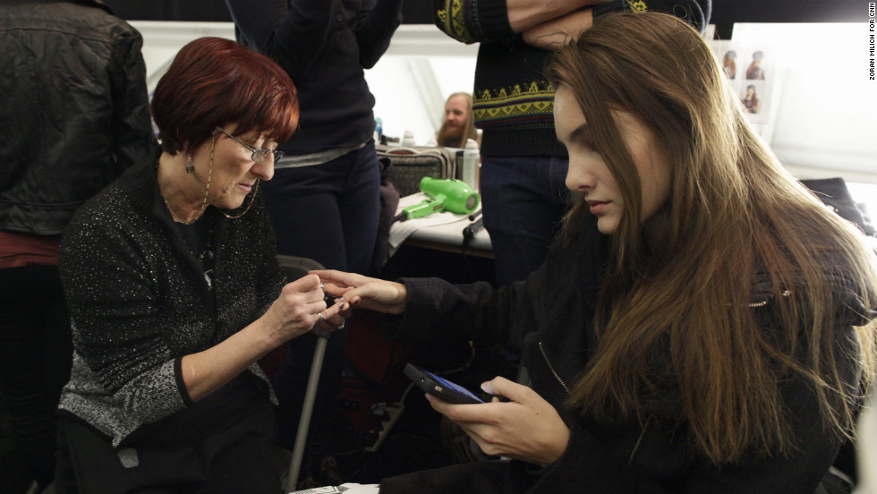 A model checks her phone while getting her nails done backstage on February 6.