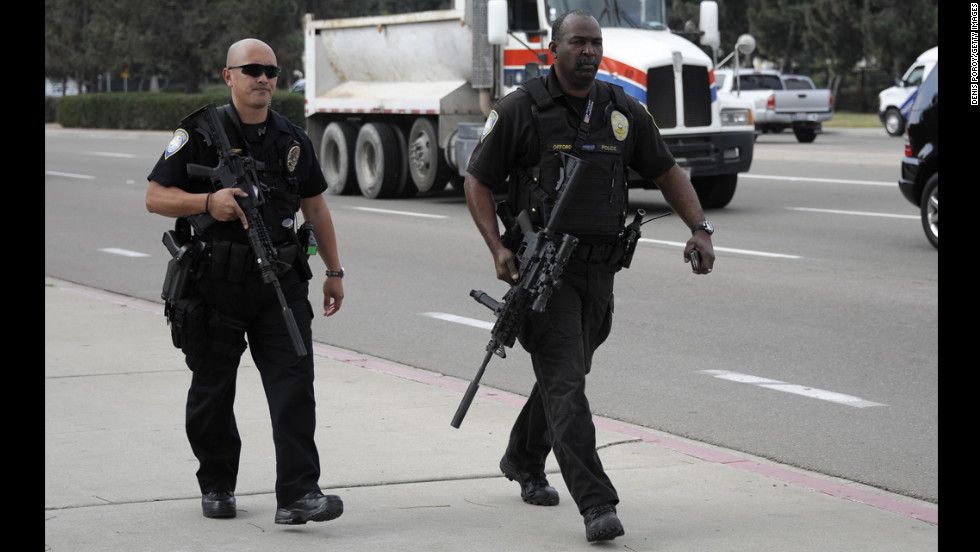 San Diego Harbor Police officers near Naval Base Point Loma armed with high-powered firearms walk along a street on February 7 in San Diego.