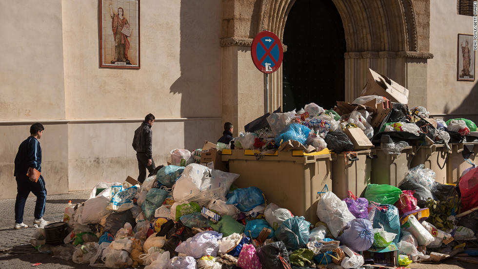 Pedestrians walk past a large pile of uncollected garbage on Thursday, February 7, the 11th day of a strike by garbage collectors protesting pay cuts and working hours. About 6,000 tons of rubbish has been left uncollected since the strike started. The management of Lipasam, Seville's municipal street cleaning company, rejected a plan by the city council to reduce the garbage collectors' wages by 5% while increasing their working hours, local media reported.