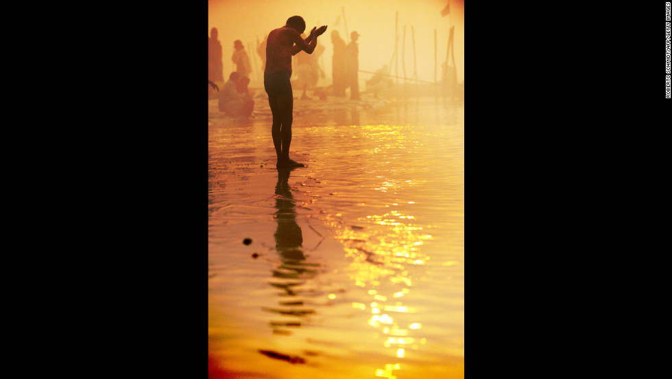 A devotee prays at day break while taking a dip at the Sangam on January 13.