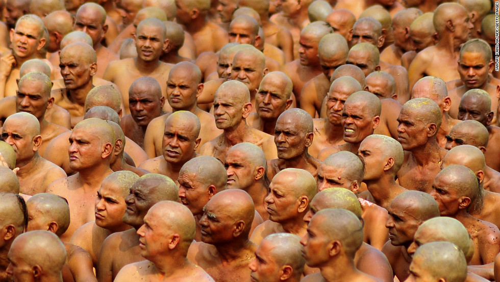 "Newly initiated Naga Sadhus, translated ""naked holy men,"" prepare to perform rituals on the banks of the Ganges River on February 6. The men wear little to no clothing during the rituals, which include running into the river to bathe."