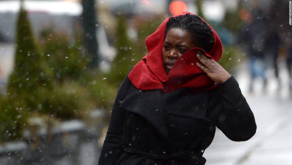 A woman tries to shield herself from wind and precipitation as the beginnings of a large winter storm hits the New York area on February 8.