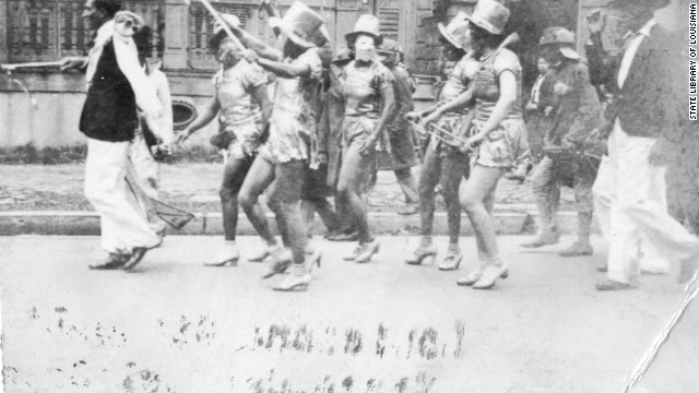 In a photo from the State Library of Louisiana, women wear Baby Doll-style costumes in a 1930s street parade.