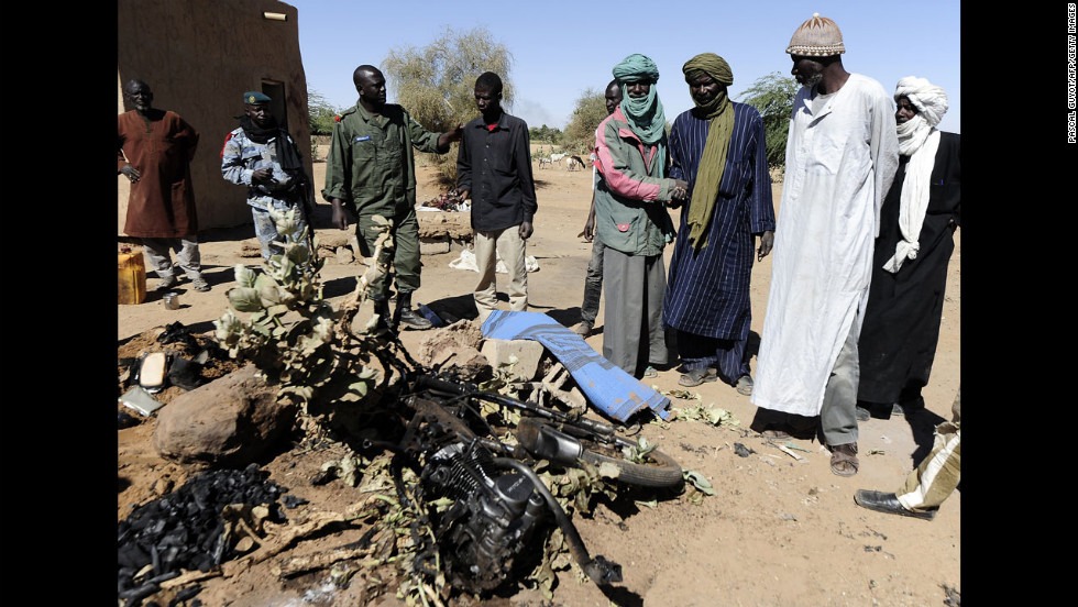 Malians look at the charred motorcycle used by a suicide bomber before he blew himself up near a group of Malian soldiers on February 8. The act marked the first suicide attack in the embattled west African nation since the start of a French-led offensive to oust the Islamists from Mali's north, where they had controlled key towns for 10 months.